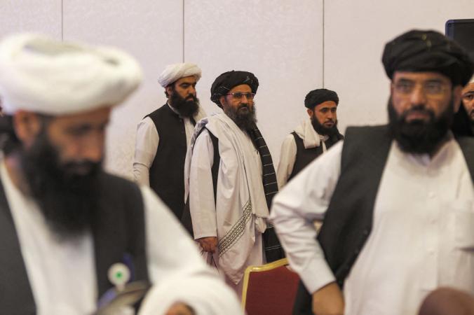 Лидер переговорной группы талибов мулла Абдул Гани Барадар (в центре) идёт после окончательного объявления мирных переговоров между афганским правительством и талибами в столице Катара Дохе 18 июля 2021 года. (Photo by KARIM JAAFAR / AFP) (Photo by KARIM JAAFAR/AFP via Getty Images) | Epoch Times Россия