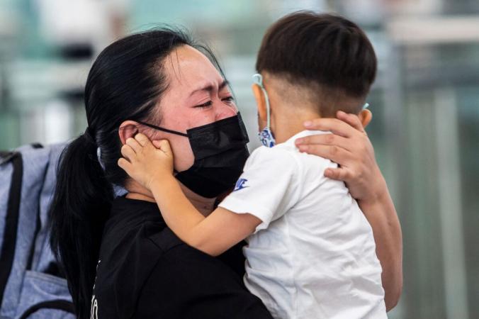 Женщина обнимает маленького ребёнка у выхода на посадку в международном аэропорту Гонконга 19 июля 2021 г. (ISAAC LAWRENCE/AFP via Getty Images) | Epoch Times Россия
