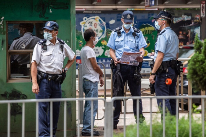 Полицейский (в центре справа) читает листовку, найденную во время обыска мужчины (2 слева) у здания Высокого суда в Гонконге 30 июля 2021 года. Это был Тон Ин-кит, которого приговорили за листовку к девяти годам тюремного заключения за терроризм и подстрекательство в ходе первого судебного процесса, проведенного в соответствии с законом о национальной безопасности, введённым Китаем. (Isaac Lawrence/AFP via Getty Images)   Epoch Times Россия