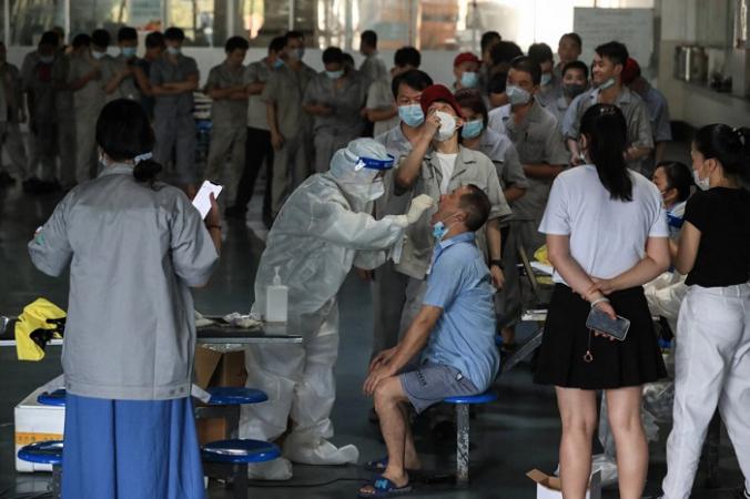 Рабочий проходит тест на COVID-19 на заводе по производству автомобильных запчастей в Ухане, провинция Хубэй в центральном Китае, 4 августа 2021 г. (STR/AFP via Getty Images) | Epoch Times Россия