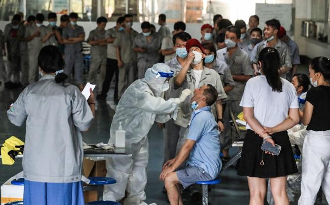 Рабочий проходит тест на COVID-19 в столовой завода по производству автомобильных запчастей в Ухане, провинция Хубэй в центральном Китае, 4 августа 2021 г. (STR/AFP via Getty Images) | Epoch Times Россия