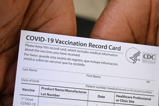 Медицинский работник показывает карточку вакцинации COVID-19 во время посещения клиники вакцинации и здоровья в центре здравоохранения QueensCare в латиноамериканском районе Лос-Анджелеса, Калифорния, 11 августа 2021 г. (Robyn Beck/AFP via Getty Images)   Epoch Times Россия