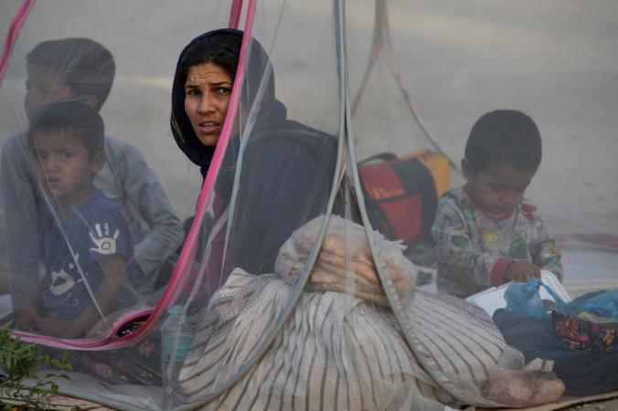 Афганцы сидят в палатке во временном лагере в парке Шари-э-Нау 12 августа 2021 года в Кабуле, Афганистан. Люди бегут в Кабул от наступающих талибов, наводняя столицу Афганистана. Paula Bronstein/Getty Images | Epoch Times Россия