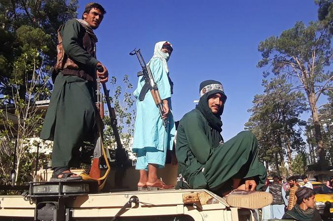 На этом снимке, сделанном 13 августа 2021 года, боевики «Талибана» стоят на машине у дороги в Герату, третий по величине городе Афганистана, после того, как правительственные войска вышли из города после нескольких недель осады. AFP via Getty Images   Epoch Times Россия