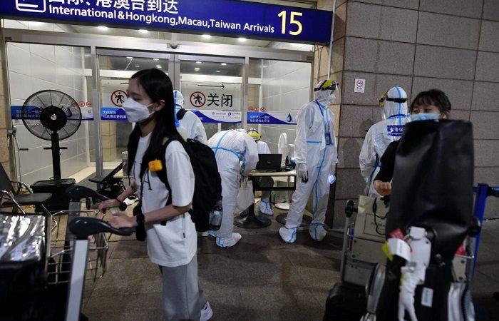 Работники аэропорта Пудун в защитной одежде помогают прибывающим пассажирам сесть в автобусы, которые отвезут их в карантинные отели в Шанхае 13 августа 2021 года. (Greg Baker/AFP)   Epoch Times Россия
