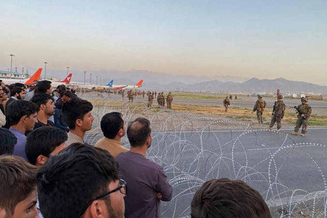 Афганцы (слева) толпятся в аэропорту, пока американские солдаты стоят на страже в Кабуле 16 августа 2021 г. SHAKIB RAHMANI/AFP via Getty Images   Epoch Times Россия