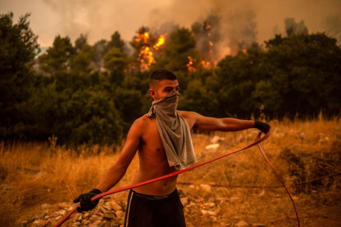 Волонтёр держит водяной шланг во время попытки тушить пожар в деревне Вилла на северо-западе Афин 18 августа 2021 года. Photo by ANGELOS TZORTZINIS/AFP via Getty Images | Epoch Times Россия