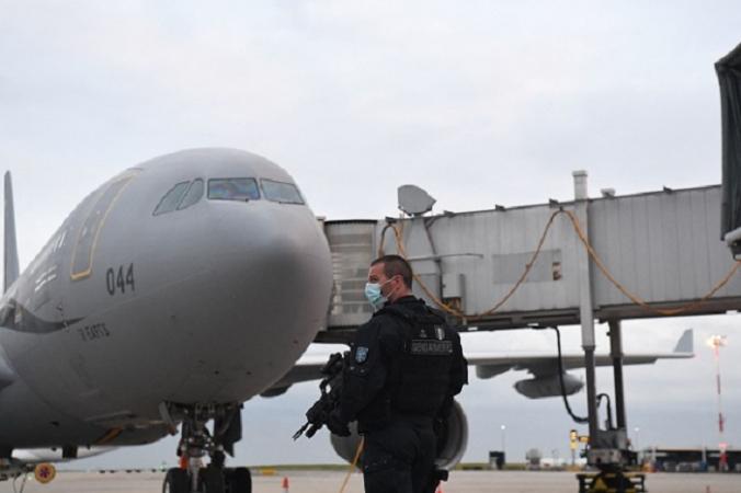 Французский жандарм охраняет стоянку самолёта Airbus A330 французской военной авиации после приземления с пассажирами из Афганистана в аэропорт Руасси им. Шарля Де Голля 18 августа 2021 года. Photo par Alain JOCARD / AFP via Getty Images.   Epoch Times Россия