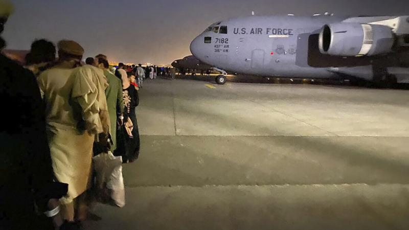 Афганцы выстраиваются в очередь, чтобы сесть на военный самолёт США, который должен покинуть Афганистан, в военном аэропорту в Кабуле 19 августа 2021 года после захвата Кабула талибами. (Shakib Rahmani/AFP via Getty Images)     Epoch Times Россия