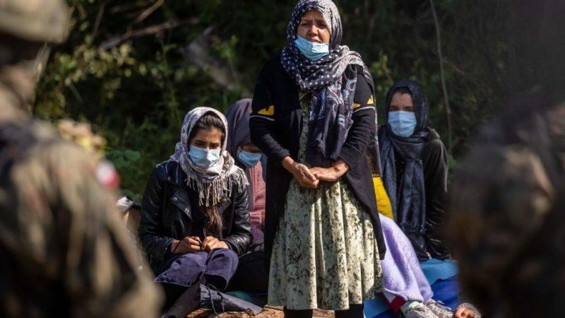 Афганские беженцы стоят перед польскими пограничниками в небольшой деревне Уснарз Горный недалеко от Белостока, на северо-востоке Польши, недалеко от границы с Беларусью, 20 августа 2021 года. WOJTEK RADWANSKI/AFP via Getty Images | Epoch Times Россия