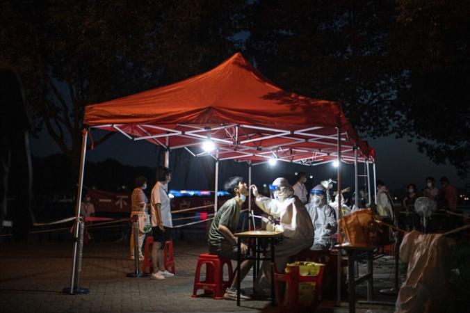 Медицинский работник берёт образцы во время массового тестирования на COVID-19 в жилом квартале в Ухане, провинция Хубэй, Китай, 6 августа 2021 года (Getty Images) | Epoch Times Россия