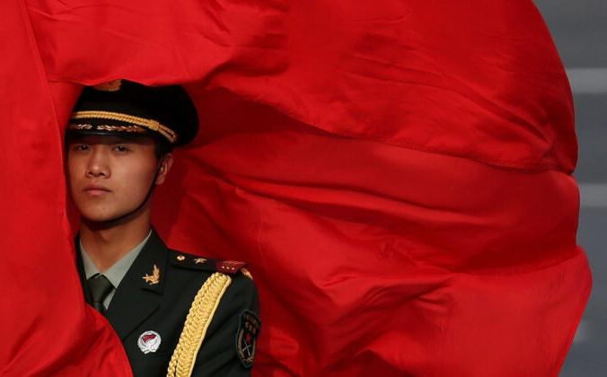 Ветер развевает красный флаг в лицо китайскому охраннику перед церемонией встречи премьер-министра Австралии Джулии Гиллард у Большого зала народа 9 апреля 2013 года в Пекине, Китай. (Фото Фэн Ли / Getty Images) | Epoch Times Россия