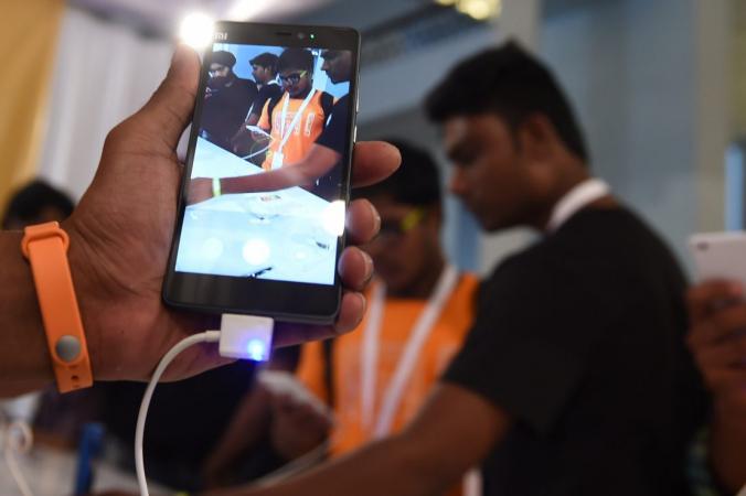 Смартфон Xiaomi Mi4i и фитнес-трекер Mi Band. Исследование показало, что слабые места в безопасности многих популярных фитнес-трекеров могут позволить хакерам получить доступ к пользовательским данным или потенциально манипулировать ими. (ДЕНЬГИ ШАРМА / AFP / Getty Images) | Epoch Times Россия