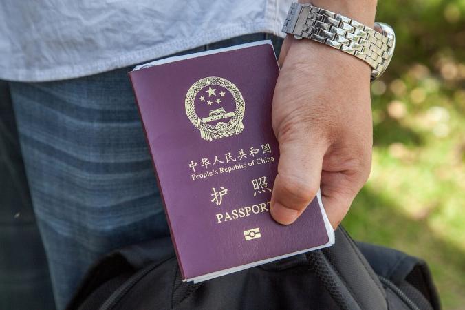 Гражданин Китая держит свой паспорт после того, как ему поставили штамп для въезда в Камбоджу на пограничном переходе. (Omar Havana/Getty Images)   Epoch Times Россия