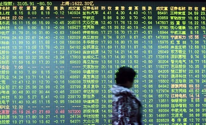 Инвестор проходит мимо экрана, показывающего движение фондового рынка в компании по ценным бумагам в Ханчжоу, Китай, 11 января 2016 г. (STR / AFP / Getty Images) | Epoch Times Россия
