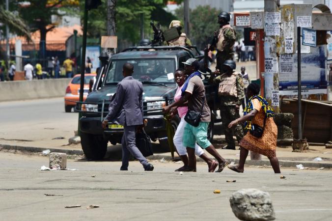 Люди проходят мимо солдат Республиканской гвардии, стоящих наулице, идущей квоенному лагерю Акуэдо вАбиджане, Кот-д'Ивуар, 15мая 2017г. (Sia Kambou / AFP / Getty Images) | Epoch Times Россия
