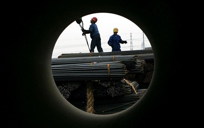 Рабочие разгружают сталь на биржевом рынке стальной продукции в Шанхае, Китай, 6 апреля 2005 г. (Photo by China Photos/Getty Images) | Epoch Times Россия