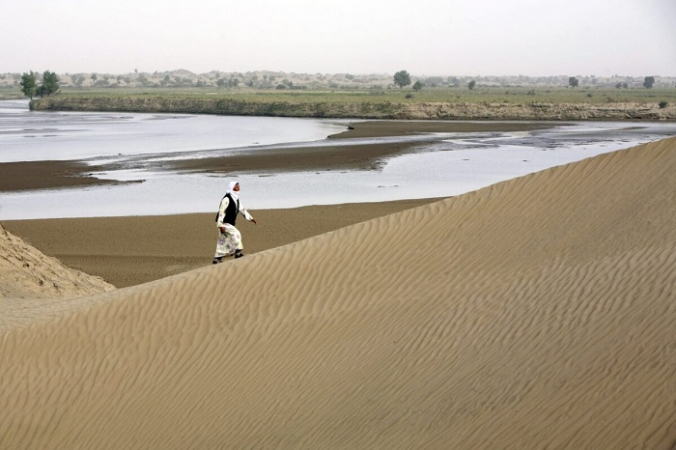 Житель Кежиянь гуляет по песчаным дюнам вдоль реки Кежиянь в деревне Дахэянь в уезде Юйтянь провинции Синьцзян, Китай, 10 сентября 2007 г. (China Photos / Getty Images) | Epoch Times Россия
