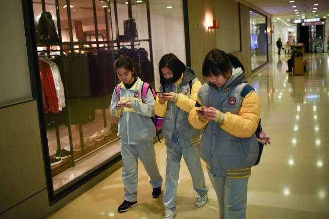 Ученицы не отрываются от мобильных телефонов во время прогулки по торговому центру в Пекине, Китай, 26 января 2018 г. (Ван Чжао / AFP через Getty Images) | Epoch Times Россия