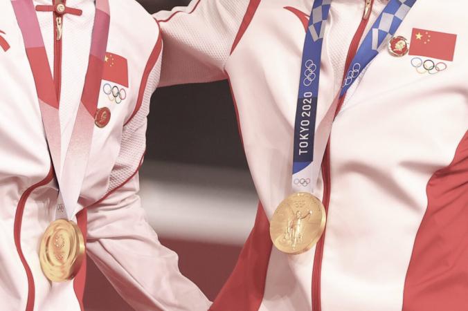 Золотые медалисты Бао Шаньцзюй из Китая и Чжун Тяньши из Китая позируют со значками бывшего лидера Коммунистической партии Китая Мао Цзэдуна, прикрепленными к их спортивным костюмам, на церемонии награждения медалями женского командного спринта по велоспорту на Олимпийских играх 2020 года в Токио на Велодроме Идзу в Сидзуока, Япония, 2 августа 2021 г. (Matthew Childs / Reuters)   Epoch Times Россия