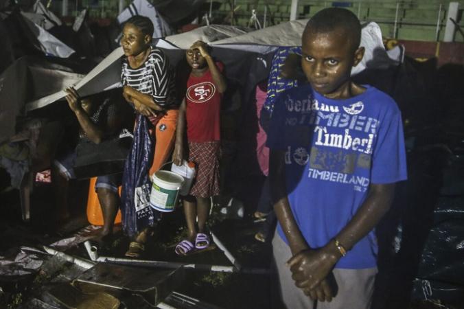Люди, пострадавшие от землетрясения в субботу, укрываются от дождя во время шторма «Грейс» в лагере беженцев в Ле-Ке, Гаити, 16 августа 2021 г. (Joseph Odelyn / AP Photo) | Epoch Times Россия