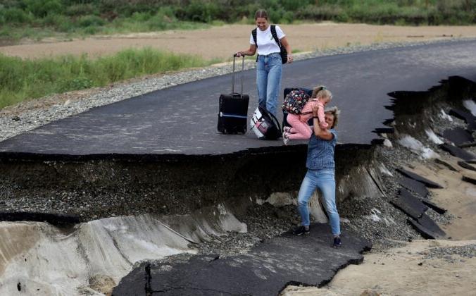 Туристы пытаются пройти по размытой наводнением дороге в районе села Цыбанобалка Краснодарского края, Россия, 14 августа 2021 г. (AP Photo) | Epoch Times Россия