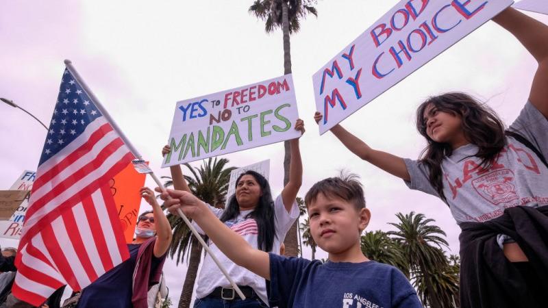 Протестующие с плакатами на демонстрации во время митинга против паспортов без вакцинации в Санта-Монике, штат Калифорния, 21 августа 2021 г. (Ринго Чиу / AFP через Getty Images)    Epoch Times Россия