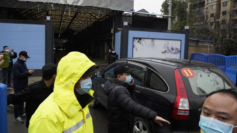 Сотрудники службы безопасности расчищают путь для команды ВОЗ, которая должна выйти на рынок морепродуктов Хуанань на третий день полевого визита в Ухане в провинции Хубэй в центральном Китае, 31 января 2021 г. (Ng Han Guan/AP Photo)  | Epoch Times Россия