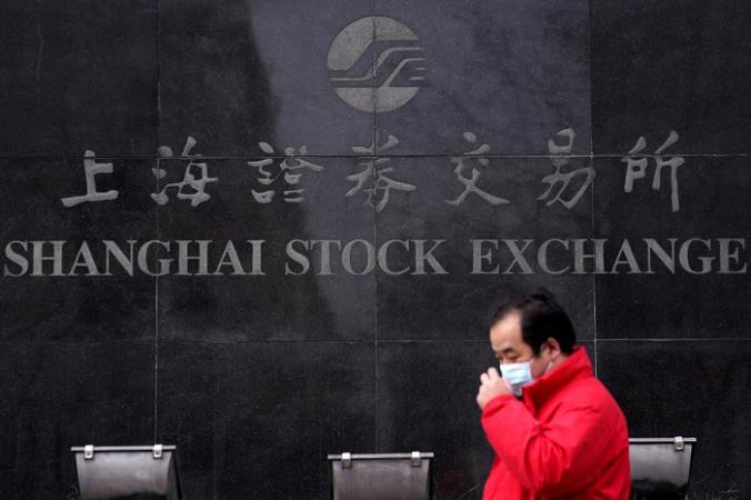 Мужчина в маске возле здания Шанхайской фондовой биржи. Шанхай, 3 февраля 2020 года. (Фото Aly Song/Reuters)   Epoch Times Россия
