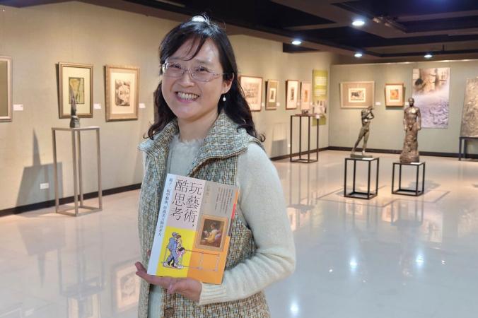 Тайваньская писательница Ирис Чанг держит свою книгу «Игра с искусством» в салоне с работами тайваньской художницы ЮЮ Янга в Тайбэе, Тайвань, 23 марта 2021 г. (Chiang Ying-ying / AP Photo)   Epoch Times Россия