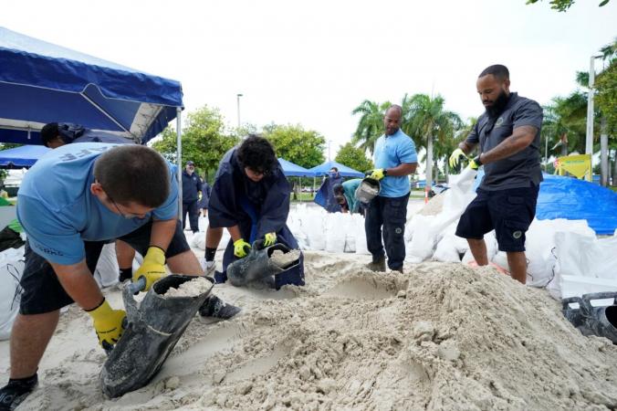 Городские рабочие заполняют мешки спеском для жителей перед началом дождей, связанных стропическим циклоном «Фред», вГрейпленд-парке вМайами, штат Флорида, 13августа 2021г. (Wilfredo Lee / APPhoto)   Epoch Times Россия