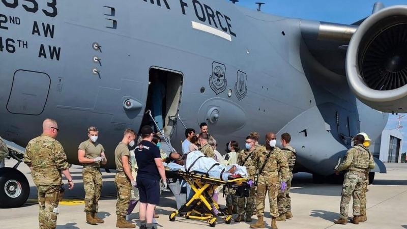 Медицинский вспомогательный персонал помогает афганской матери покинуть самолёт C-17 ВВС США через несколько мгновений после того, как она родила ребёнка на борту после приземления на авиабазе Рамштайн, Германия, 21 августа 2021 г. (U.S. Air Mobility Command via Reuters) | Epoch Times Россия