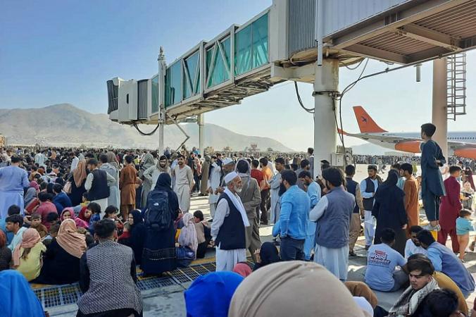 Афганцы толпятся на взлетно-посадочной полосе аэропорта в Кабуле, надеясь покинуть контролируемый талибами Афганистан, после того как президент Ашраф Гани бежал из страны и признал, что повстанцы выиграли 20-летнюю войну. 16 августа 2021 года. (AFP via Getty Images)   Epoch Times Россия