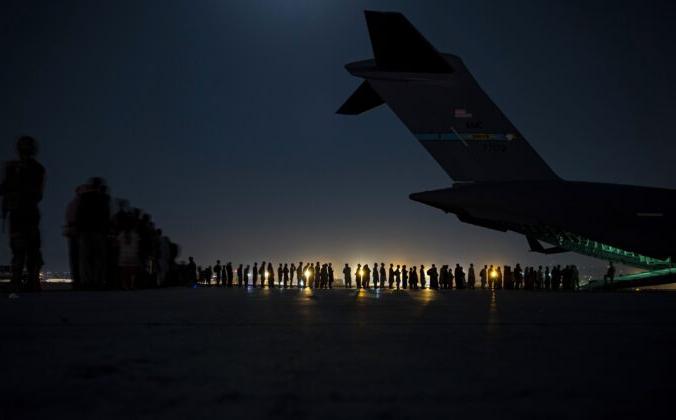 In this image provided by the U.S. Air Force, U.S. AЭкипаж ВВС США, входящий в состав 816-й экспедиционной авиационной эскадрильи, готовится загрузить эвакуированных на борт самолёта C-17 Globemaster III ВВС США в международном аэропорту имени Хамида Карзая, Кабул, Афганистан, 21 августа 2021 года. (Старший лётчик Тейлор Крул / ВВС США через AP)ir Force aircrew, assigned to the 816th Expeditionary Airlift Squadron, prepare to load qualified evacuees aboard a U.S. Air Force C-17 Globemaster III aircraft in support of the Afghanistan evacuation at Hamid Karzai International Airport, Kabul, Afghanistan, Saturday, Aug. 21, 2021. (Senior Airman Taylor Crul/U.S. Air Force via AP) | Epoch Times Россия