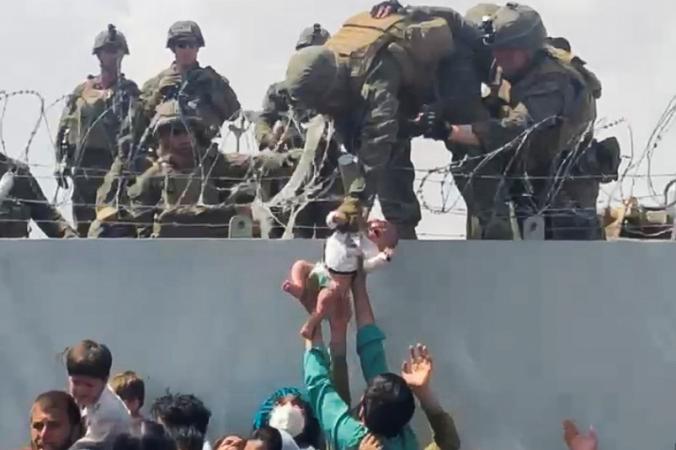 Младенца передают американской армии через стену аэропорта в Кабуле, Афганистан, 19 августа 2021 г. (Omar Haidari via Reuters) | Epoch Times Россия