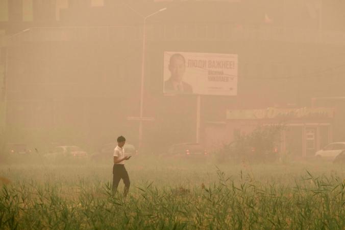 Мальчик идёт сквозь дым от лесного пожара, охватившего Якутск, столицу республики Саха (Якутия), Дальний Восток, Россия, 12 августа 2021 г. (Ivan Nikiforov/AP Photo)   Epoch Times Россия