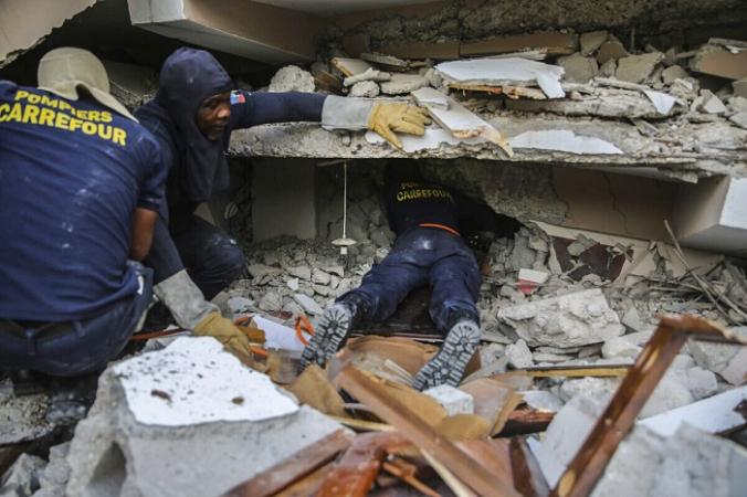 Пожарные ищут выживших внутри разрушенного здания после субботнего землетрясения магнитудой 7,2 в Ле-Ке, Гаити, в воскресенье, 15 августа 2021 г. (AP Photo / Joseph Odelyn) | Epoch Times Россия