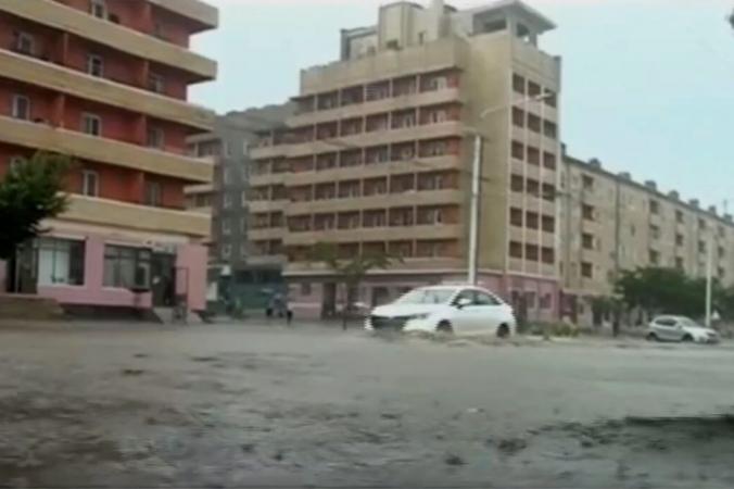 Автомобили проезжают по затопленным улицам после проливных дождей в провинции Хамгён-Намдо в Северной Корее. (KRT via APTV) | Epoch Times Россия