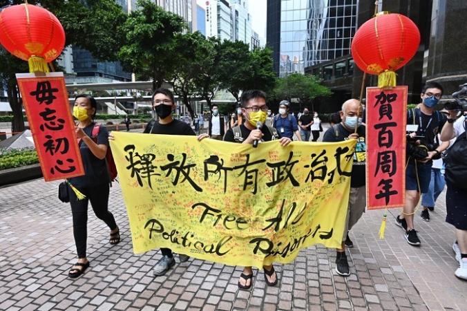 Четыре члена Гонконгской лиги социал-демократов проходят маршем по улицам, призывая пекинский режим освободить всех политических заключённых в Гонконге, 1 июля 2021 года. (Song Bilong/The Epoch Times)   Epoch Times Россия
