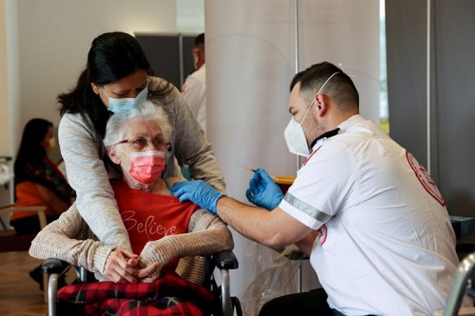 Пожилая женщина получает ревакцинацию против COVID-19 в доме престарелых в Нетании, Израиль, 19 января 2021 года. (Ronen Zvulun/Reuters)   Epoch Times Россия