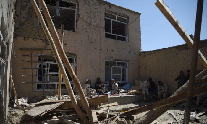 Афганские жители сидят в разрушенном дворе, пьют чай после авиаудара НАТО по дому в Кабуле 28 сентября 2017 г. (Вакил Косар / AFP через Getty Images)    Epoch Times Россия