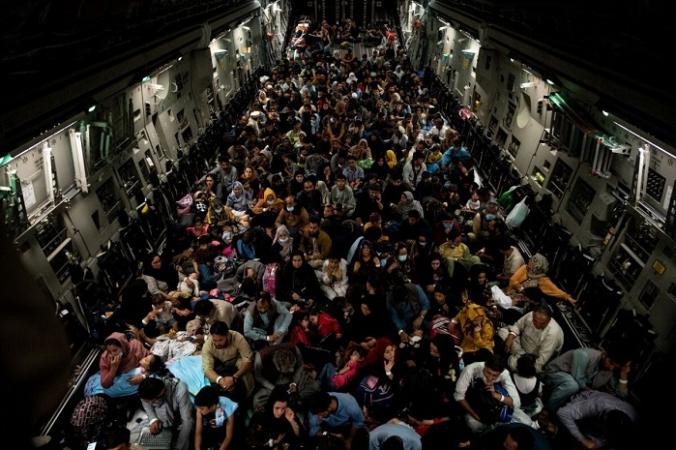 Афганцы сидят в военном самолёте во время эвакуации из Кабула 19 августа 2021 г. (Staff Sgt. Brandon Cribelar/U.S. Marine Corps/Handout via Reuters) | Epoch Times Россия