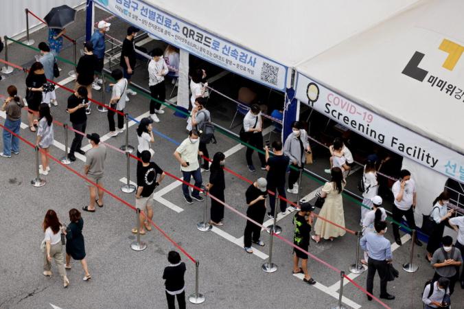 Люди ждут в очереди на тест на COVID-19 на полигоне, который временно открыт в центре общественного здравоохранения в Сеуле, Южная Корея, 9 июля 2021 г. (Heo Ran / Reuters)   Epoch Times Россия