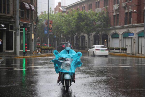 Житель проезжает по улице во время дождя в Шанхае, Китай, 13 сентября 2021 г. Chen Si / AP Photo