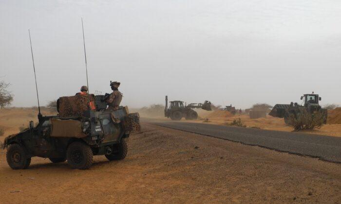 Два солдата антитеррористической миссии Бархейн в регионе Сахель в Африке на лёгкой бронированной машине наблюдают за строительством новой французской базы в Госси, в центре Мали, 25 марта 2019 г. Daphne Benoit/AFP via Getty Images   Epoch Times Россия