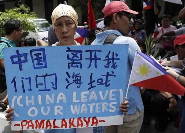 Протестующая держит плакат на митинге у китайского консульства в финансовом районе Макати столичного города Манила на Филиппинах по случаю Дня независимости 12 июня 2019 года. Aaron Favila/AP