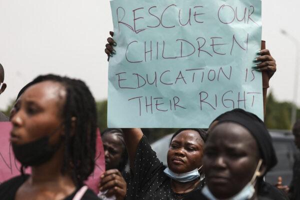 Родители и родственники учеников Федерального колледжа механизации лесного хозяйства в Кадуне, которые были похищены, держат плакаты во время демонстрации в Абудже, Нигерия, 4 мая 2021 г. Kola Sulaimon/AFP via Getty Images