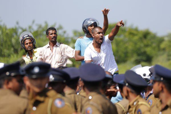 Жители выкрикивают лозунги во время акции протеста в деревне Мириджавила в Амбалантоте, Шри-Ланка, 7 января 2017 года. Полиция Шри-Ланки использовала водомёты, чтобы попытаться разогнать жестокие столкновения между сторонниками правительства и сельскими жителями, протестующими против захвата частной земли для создания промышленной зоны, в которой Китай будет иметь основную долю. Правительство Шри-Ланки подписало соглашение о 99-летней аренде порта Хамбантота с компанией, в которой Китай будет владеть 80% акций. Официальные лица также планируют создать неподалёку промышленную зону, где китайским компаниям будет предложено открыть фабрики. AP Photo / Eranga Jayawardena