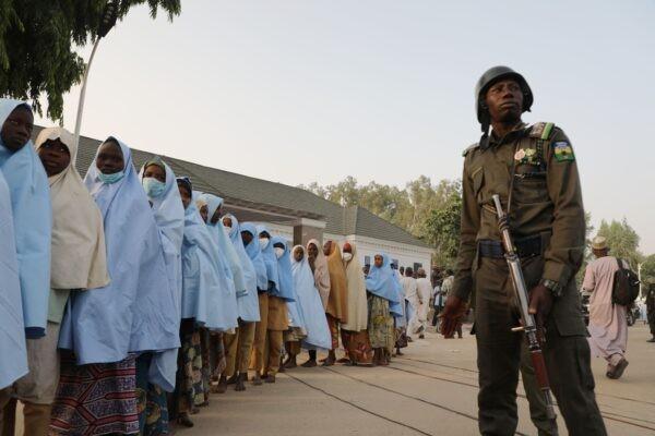 Солдат стоит рядом с группой девочек, похищенных из школы-интерната на севере Нигерии, у Дома правительства в Гусау, штат Замфара, 2 марта 2021 г. AFP via Getty Images