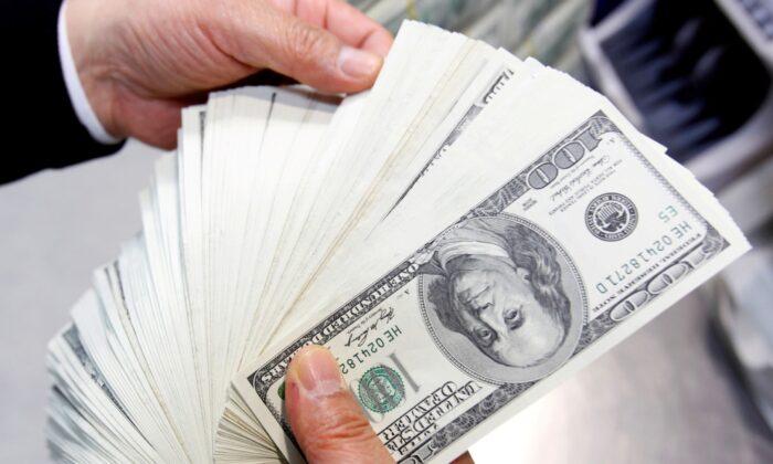 Сотрудник Korea Exchange Bank пересчитывает 100-долларовые банкноты США во время фотосессии в штаб-квартире банка в Сеуле, Южная Корея, 28 апреля 2010 г. Jo Yong-Hak / Reuters   Epoch Times Россия